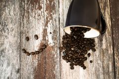 Black Ceramic Cup With Coffee Beans All on Brown Wooden Surface royalty free stock photography