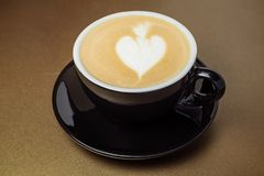 Black ceramic cup of coffee with cream looks like a hart and mug. Black cup of coffee with cream looks like a hart and mug close-up on background royalty free stock photo