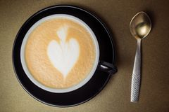 Black ceramic cup of coffee with cream looks like a hart, spoon. Black cup of coffee with cream looks like a hart, spoon and mug close-up on gold background stock photography