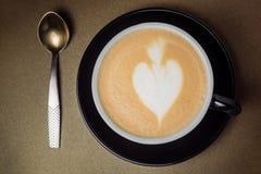 Black ceramic cup of coffee with cream looks like a hart, spoon. Black cup of coffee with cream looks like a hart, spoon and mug close-up on gold background stock photos