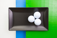 Black ceramic dish with golf balls Royalty Free Stock Photos