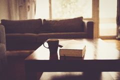 Black Ceramic Mug Beside Black Hardbound Book on Brown Wooden Coffee Table Royalty Free Stock Images