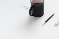 Black Ceramic Mug Beside Black Pencil on White Table Stock Photo