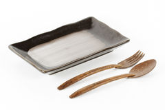 Black ceramic plate with spoon and fork Stock Image