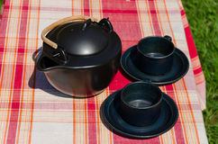 Black ceramic tea set on checked background Royalty Free Stock Image