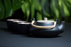Black ceramic teapot with cups. And steam Royalty Free Stock Image