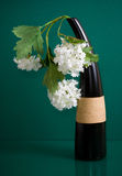 Black ceramic vase with white flowers on green Stock Photo