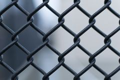 Black chain link fence against a smooth blurred out background, closeup royalty free stock images