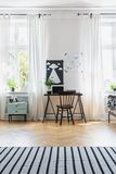 Black chair at desk in bright home office interior with windows, carpet and posters stock images
