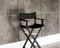 Black  chair in front of a gray wall Royalty Free Stock Photo