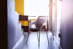 Black chair in the hallway of the apartment, a real photo with a copy of the space on the white wall. Beautiful office space. The stock image