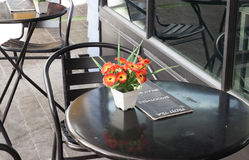 Black chair and table in outdoor cafe. Black chair with artificial orange flower on table in outdoor cafe Royalty Free Stock Photos