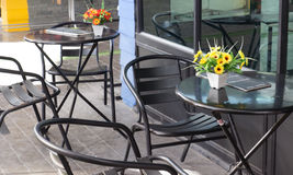 Black chair and table in outdoor cafe. Black chair and table with orange yellow flower in front of cafe Royalty Free Stock Photos
