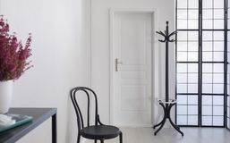 Black chair in white corridor of elegant apartment, real photo with copy space royalty free stock image