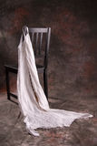 Black chair with white dress. A black chair with a white dress hanging on the corner royalty free stock images