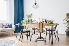 Black chairs around big table. Wooden and metal black chairs around big table in a bright dining and living room interior Stock Image