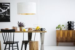 Black chairs in dining room. Black chairs at wooden table under white lamp in simple dining room interior with stool Royalty Free Stock Images