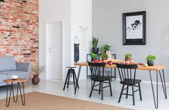Black chairs at dining table and poster in flat interior with grey sofa against red brick wall stock photo