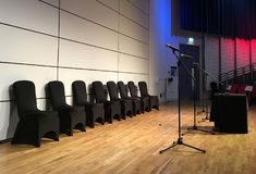 Black chairs against a white wall and microphones on a stage set up ready for presentation in auditorium. Eight black covered chairs, four microphones, and table stock photo