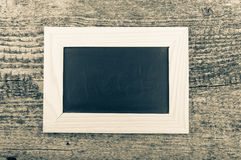Black chalk board in a light wooden frame on the old wooden tabl Royalty Free Stock Photos