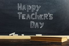 Black chalk board over wooden table with book, blank for text or background for school theme stock images