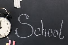 On the black chalk board written the word school with white chalk and lies the alarm clock stock photos