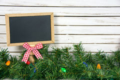 Black chalkboard in Christmas pine and lights. Chalkboard with red and white gingham bow in Christmas pine and lights Royalty Free Stock Images
