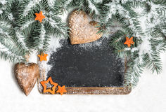 Black chalkboard among Christmas tree branches under snow Stock Image