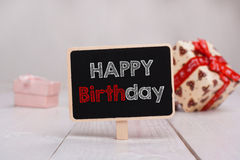 Black chalkboard with the Happy Birthday text on the table. On the background with gifts Stock Photo