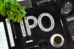 Black Chalkboard with IPO Concept. 3D Rendering. Business Concept - IPO Handwritten on Black Chalkboard. Top View Composition with Chalkboard and Office Royalty Free Stock Images