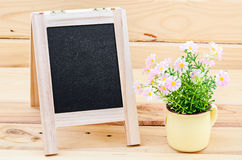 Black chalkboard lying with flowers. Stock Images