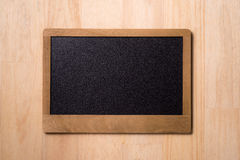 Black chalkboard over wooden table. Blank chalkboard with wood frame, erased and ready for your message.  Royalty Free Stock Photography