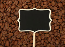 Black chalkboard sign over roasted coffee beans. Blank black chalkboard wooden sign over background of roasted brown Arabica coffee big beans pattern, close up Stock Images