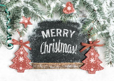 Black chalkboard on snow with caption. Merry Christmas!, toned image Royalty Free Stock Photo