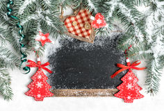 Black chalkboard on snow decorated for Christmas, text space Stock Image