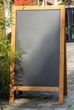 Black chalkboard stand on wood for a restaurant menu in the stre Royalty Free Stock Photo