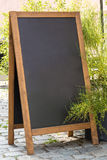 Black chalkboard stand on wood for a restaurant menu in the stre Royalty Free Stock Photos