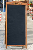 Black chalkboard stand on wood for a restaurant menu in the stre Stock Image
