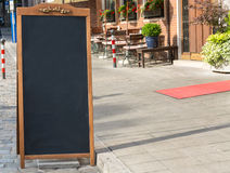 Black chalkboard stand on wood for a restaurant menu in the stre. A black chalkboard stand on wood for a restaurant menu in the street Royalty Free Stock Photography