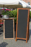 Black chalkboard stand on wood for a restaurant menu in the stre Stock Photos