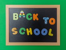 Black chalkboard with wooden frame, text back to school in colorful letters, green wall background royalty free stock images