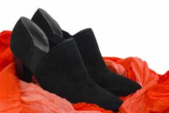 Black chamois woman's shoes on a red neck-piece. Stock Photo