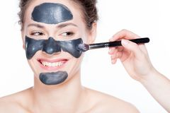 Black charcoal mask application on beautiful woman. Stock Images