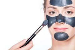 Black charcoal mask application on beautiful woman. Stock Photos