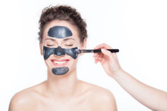 Black charcoal mask application on beautiful woman. Royalty Free Stock Photo