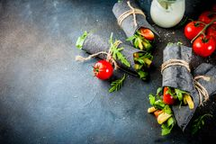 Black charcoal wraps. Trendy healthy vegan food. Black charcoal wrapped sandwiches, with fresh vegetables, cheese, on a dark blue background, space for text royalty free stock photography