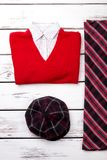 Black checkered hat and red pullover. Vertical view, bright wooden background Royalty Free Stock Images