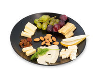 Black cheese plate with red and green grapes Stock Photos