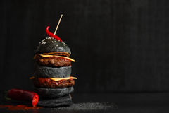 Black cheeseburger with meat. Black burger with meat, cheese, fried onion, tomato sauce and hot chili pepper on the black table royalty free stock photos