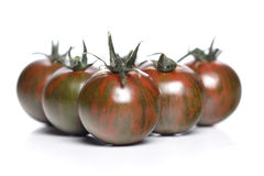 Black cherry tomatoes on white background Royalty Free Stock Images